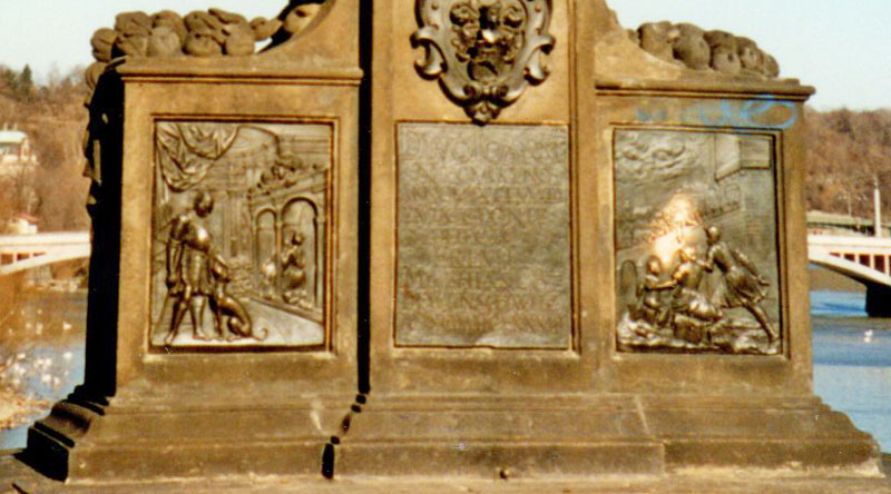 detail of the prague jan nepomuk statue showing shiny brass plaque on the right