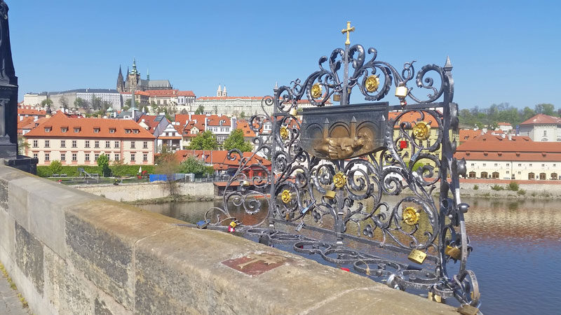 ornamental wrought ironwork above the jan nepomuk cross with river and prague castle in background
