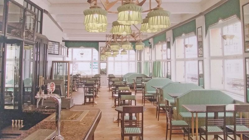 the restored interior of pragues grand cafe orient. cubist style with green and gold decor and mahogany bar
