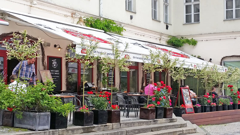 street side garden cafe called la gare in prague with stella artois awnings and potted trees
