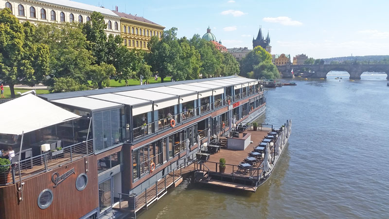 prague restaurant boat moored on the river vltava with charles bridge in the background