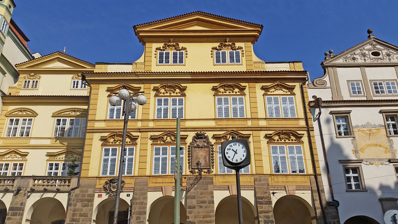 a golden yellow painted 4 floor baroque style building with stone arches