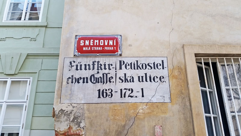 a street sign in prague showing the original street name in czech and german and the modern name