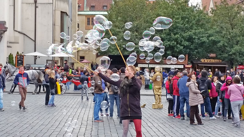a woman making bubbles from string between two sticks