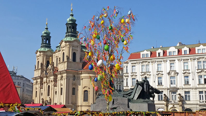 a baroque style church and neo-baroque buildings in background and an ash tree decorated with easter eggs and ribbons