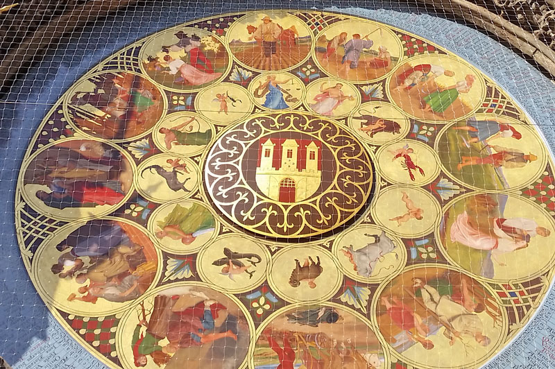 prague calendarium in 2018. hand painted face with 12 large circles showing farming actions and inside them are 12 smaller circles showing astrological zodiac signs