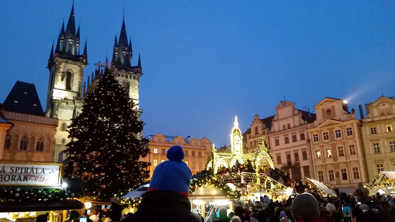 crowd of people on prague old town square waiting for the christmas tree to be lit
