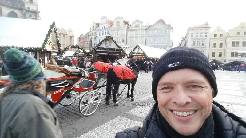 man with a black hat and behind is a horse and carriage in a prague christmas market