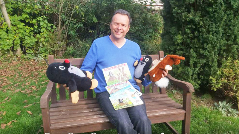 man sitting on bench with cuddly toy moles, rabbit and little mole books for kids