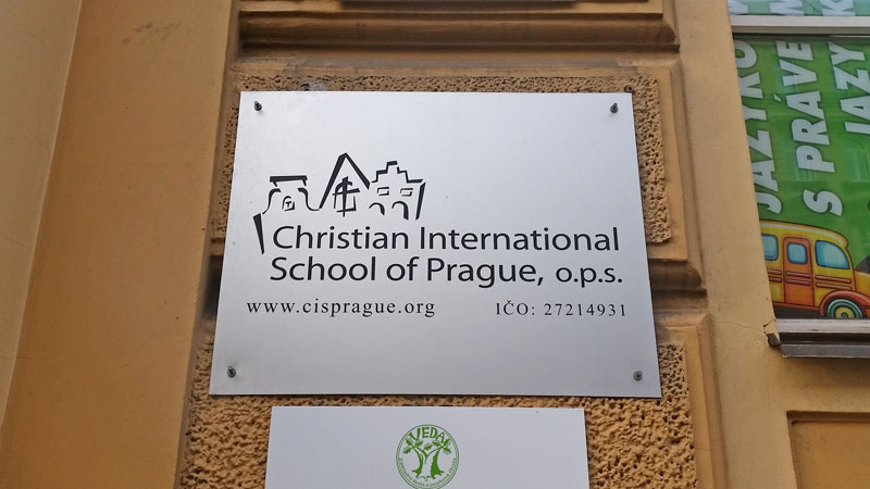 metal sign on a wall saying christian international school of prague