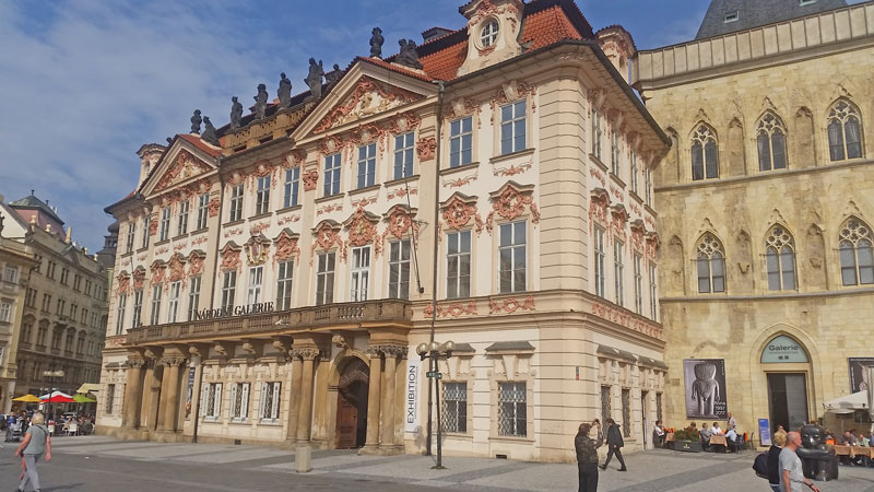 prague old town square late baroque style kinsky palace, a four floor building with stone archways joined by a first floor balcony and 2 roof level porticos