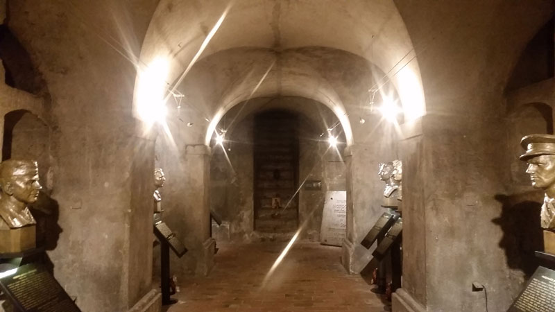 a lit cellar with bronze busts on both sides and steps at the end.