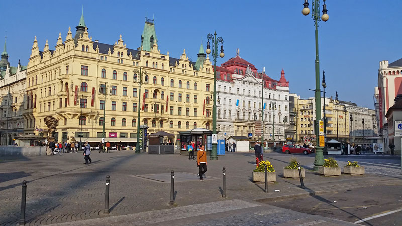 scene view of republic square in prague. cobble stone square with planted pots and art deco style street lamps