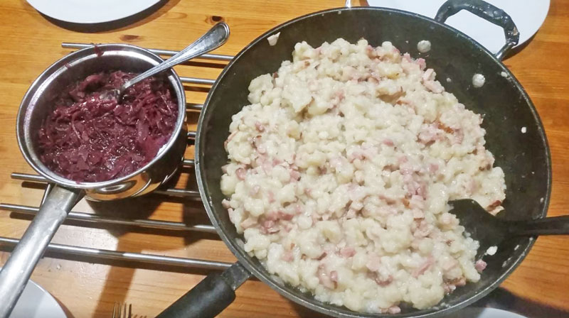 bowl of halusky (czech gnocchi) next to a bowl of heated sweet red cabbage