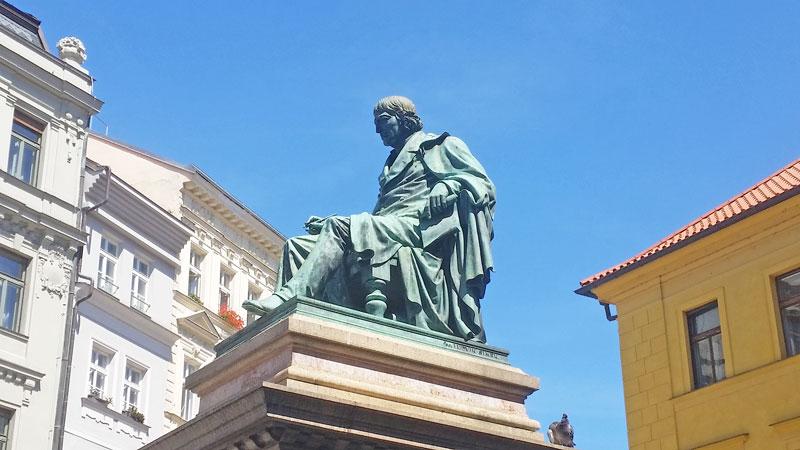 bronze seated statue of josef jungmann on a granite pedestal
