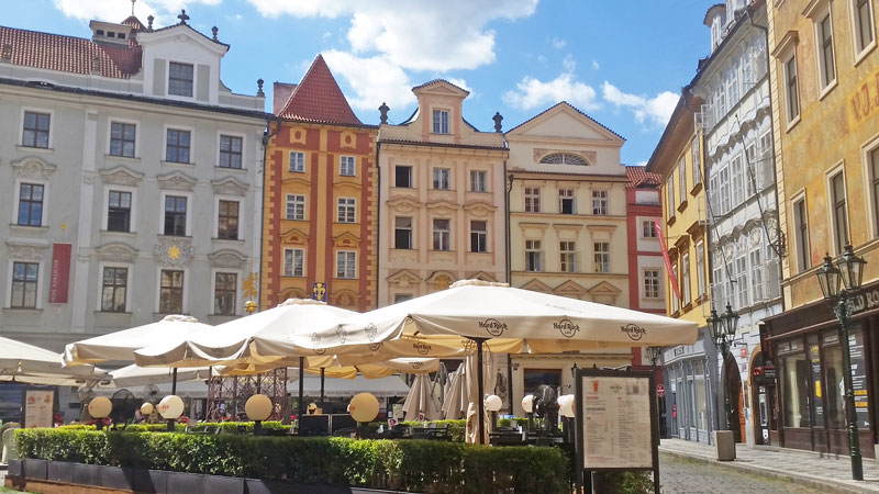 little square surrounded by colourful renaissance buildings with umbrella covered outdoor eating in the middle