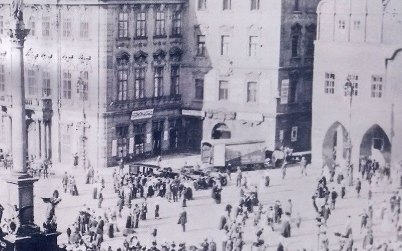black and white photo showing scene view of people and vehicles on prague old town square circa 1918