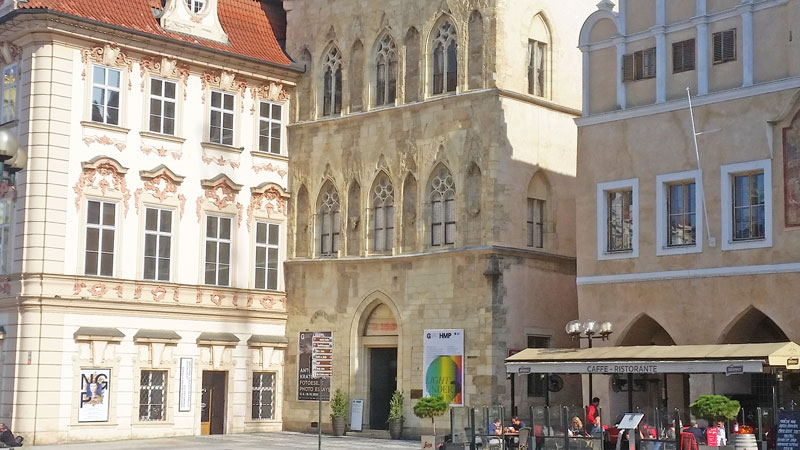 the gothic prague house at the stone bell in the centre with a renaissance style building the the right and the late baroque style kinsky palace on the left