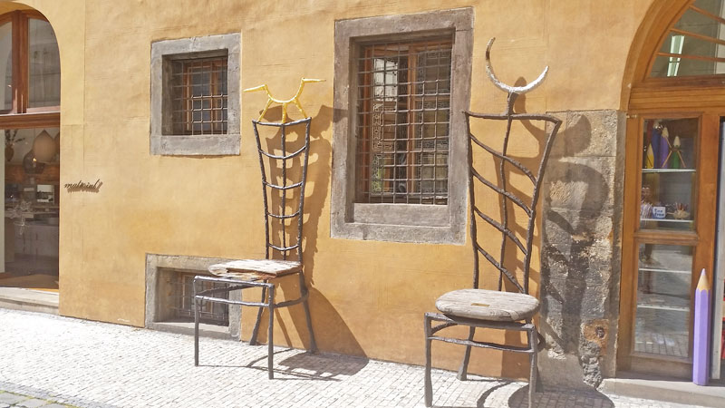 oversized artistic chairs leaning against a stuccoed gothic building in the prague tyn courtyard