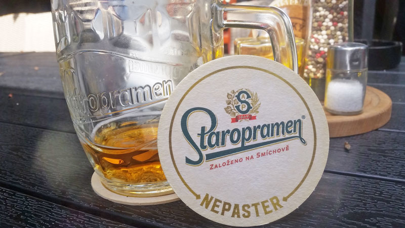 glass of staropramen beer with beer mat leaning against it