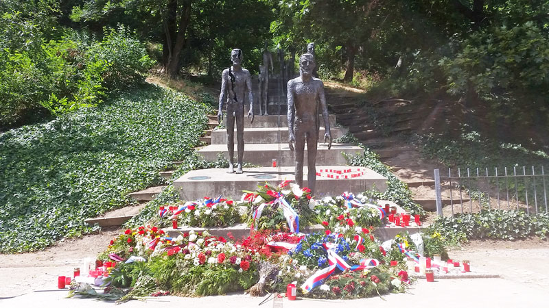 monument to victims of communism in Prague lesser town, stone steps with bronze figures, wreaths and flowers