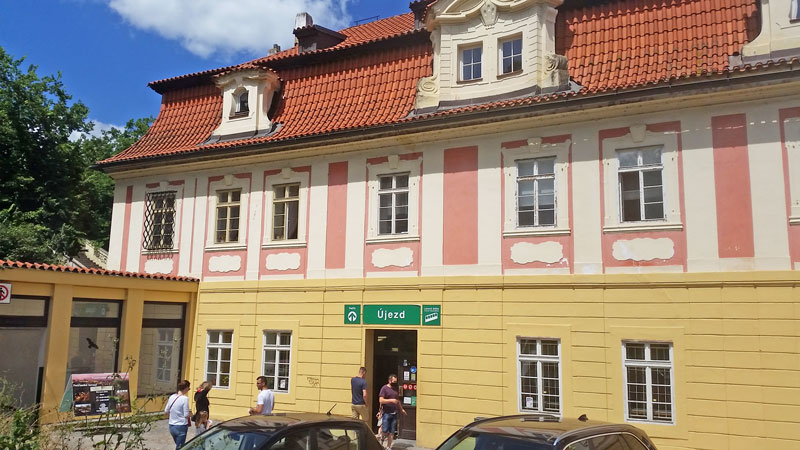 baroque style building in prague with yellow and pink facade and red tiled roof