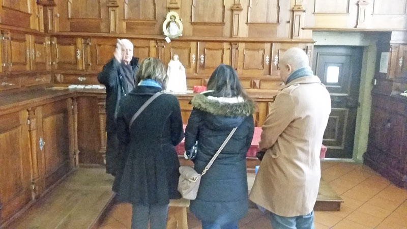 three people receiving a private blessing in the sacristy of the church of our lady victorious in prague