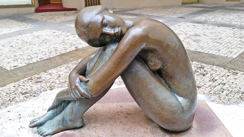 sculpture of a naked girl with knees drawn up by her arms in bronze in the prague platyz palace courtyard