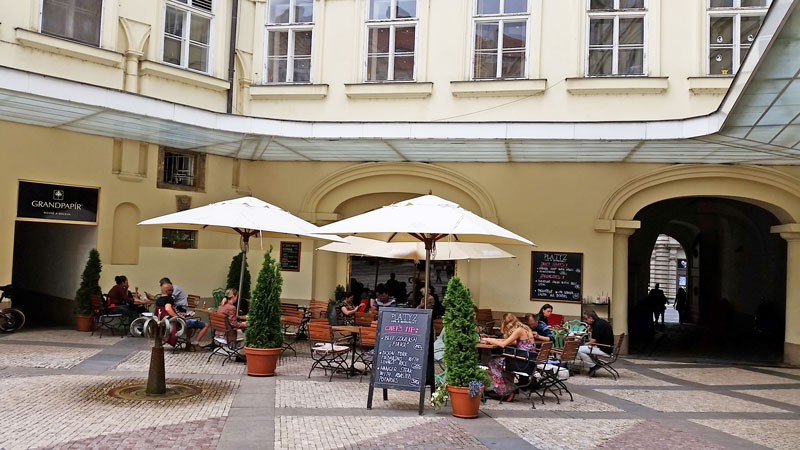 external cafe seating on the cobble stones of prague platyz courtyard