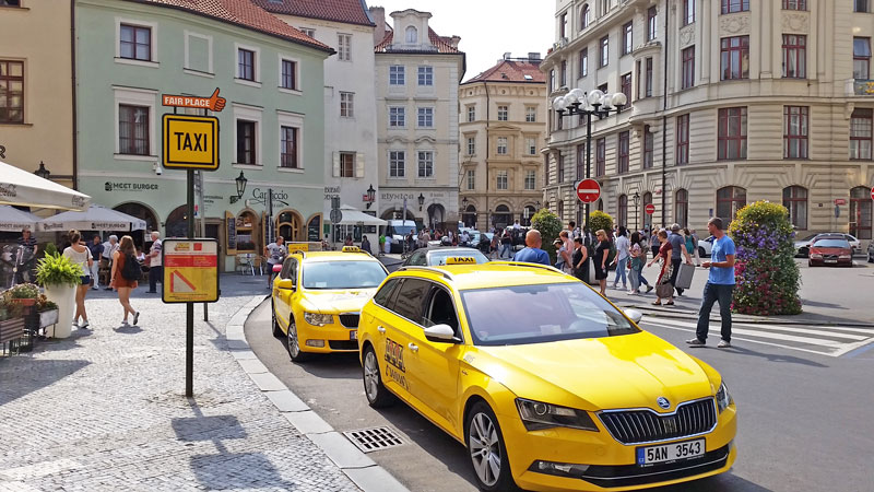 two yellow prague taxis parked at a fair place zone