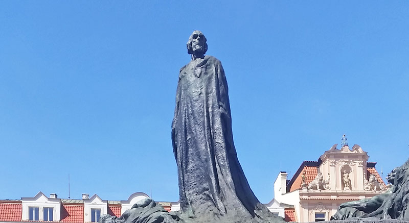 tall bronze statue of jan hus on prague old town square with blue sky background