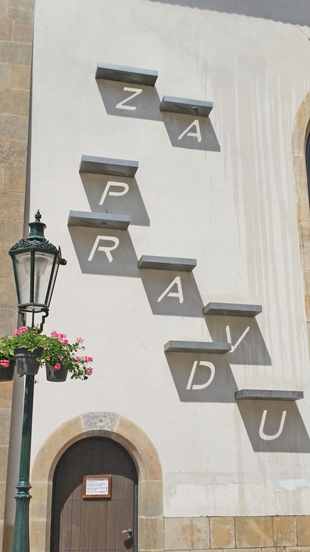 on the bethlehem chapel in prague, eight stainless steel plates with letters cut into them are projecting the words za pravdu onto the wall using sunlight