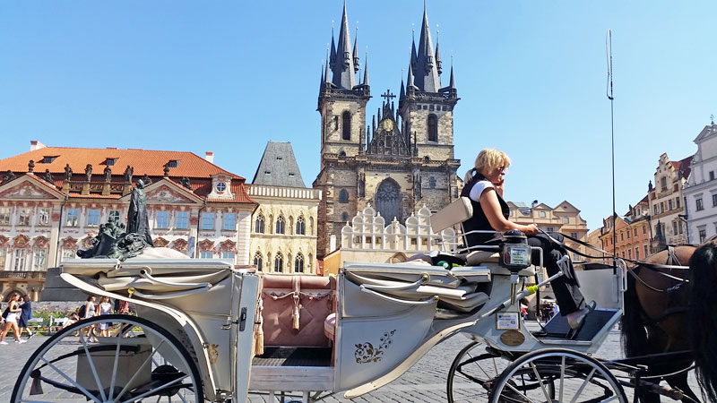 prague old town square lady driving a horse and carriage with the gothic twin tower church of our lady before tyn in the background