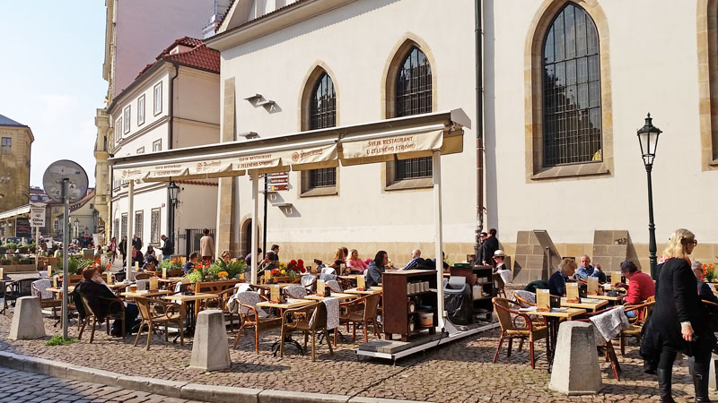 people eating outside at the Svejk restaurant on Bethlehem Square in Prague