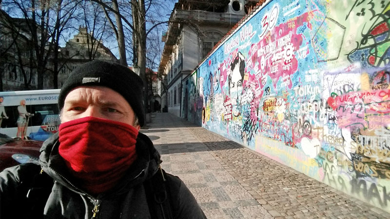 man standing all alone at the prague john lennon wall during the coronavirus lockdown