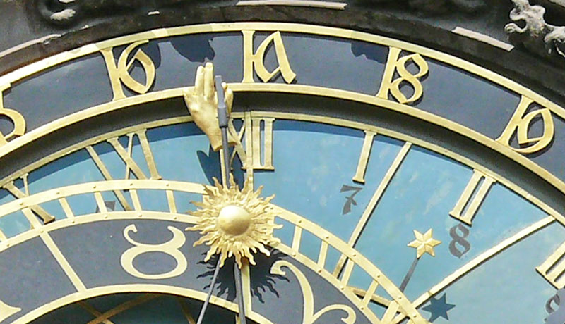 prague astronomical clock showing detail of the hand and the sun