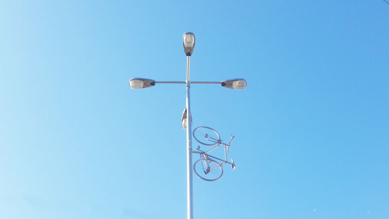 a city street lamp post in prague with 4 lights and the model of a bike on a blue sky, the memorial is called bike to heaven