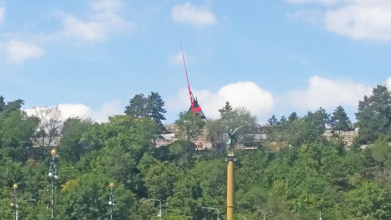 prague metronome reaching up above trees in the summer