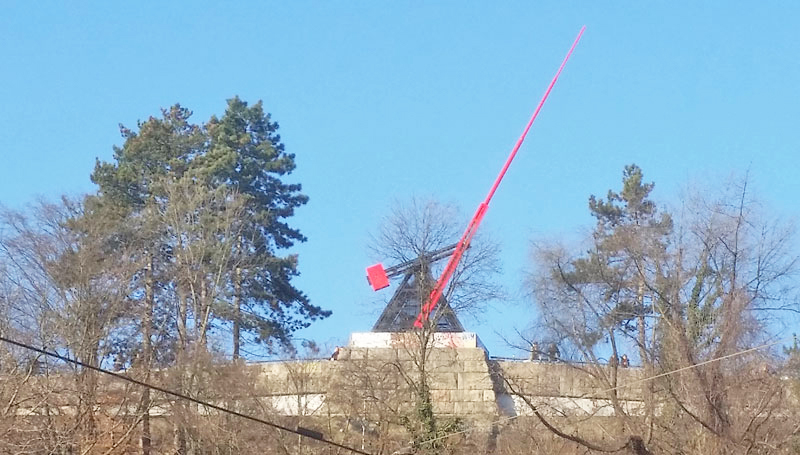the prague metronome on it's stone plinth with red pointer against a blue sky