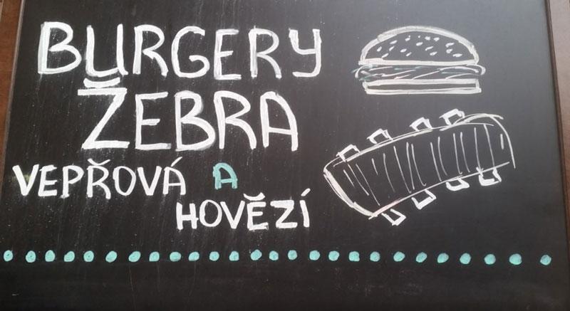 restaurant chalkboard showing burgers and ribs in czech, looks like zebra but really it is pork ribs.