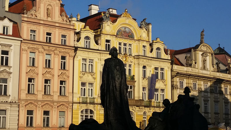 the main jan hus figure on the jan hus monument in prague silhouetted against buildings in the morning sun