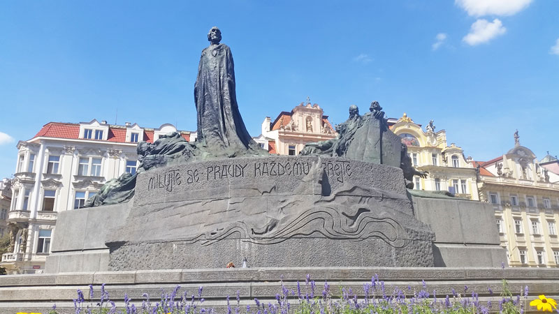 the jan hus monument on the old town square in prague with granite stone base and statues of bronze alloy which gives them a greenish black appearance