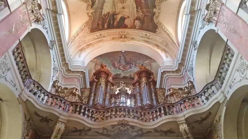 organ at prague st james basilica with balcony and fresco ceiling