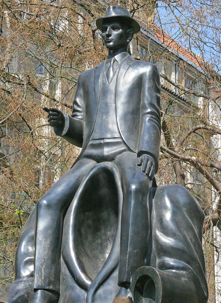 the franz kafka bronze monument in prague with him sitting on the shoulders of an empty jacket