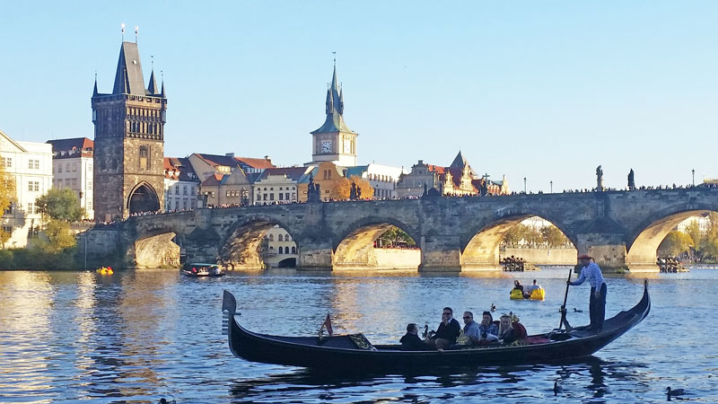 family on a gondola in Prague hired from Little Venice on the vltava river with charles bridge in the background