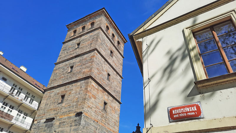 a 17th century stone water tower next to a czech street sign that translates as the way to the new mill