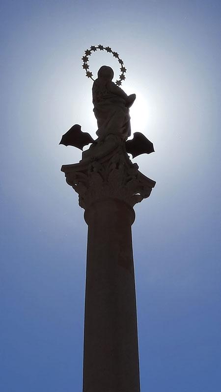 Prague Marian Column silhouetted against a blue sky