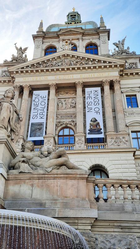 detail shot of the facade of the Prague National Museum including reclining statue and fountain