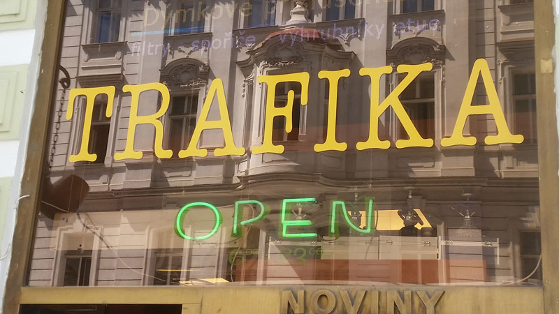 a yellow trafika or tabak sign in a shop window with the reflection of the building opposite