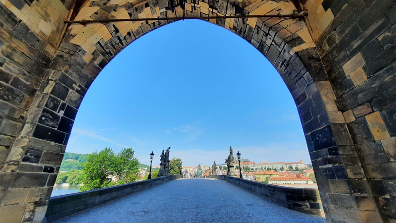 prague charles bridge scene view from under the old town gate tower showing an almost empty bridge